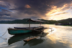 I Stand Alone (nathan gonzales) Tags: longexposure sunset sea sky sun mountain lake seascape water canon landscape asian dawn boat interesting asia skies native philippines bamboo filipino silky banca nathangonzales