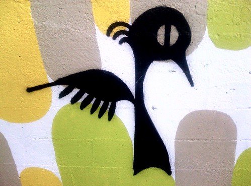 graffiti -- cartoon blackbird standing upright, wings pushed behind