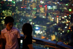 A young couple wait to have their photo taken by a professional atop a buiding amongst the lights in Roppongi
