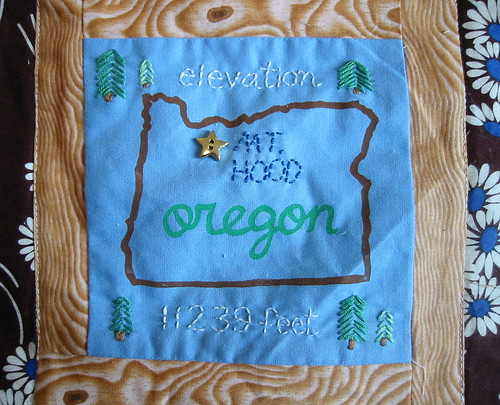 The gocco-embroidery-button Mt. Hood square on my log cabin quilt