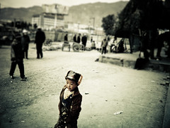 Boy - Xining (mattlindn) Tags: china street old city boy portrait people blur cute male beautiful childhood fashion kids youth children kid asia pretty alone child view candid buddhist young happiness dirty tibet clothes portraiture dreams rubbish amdo tibetan roads  atmospheric rubble 2007 reallife   qinghai xining     streetphotographycandidstreetportrait