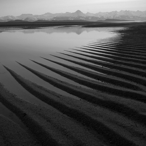 El agua en calma se retira de la playa. Al fondo, montañas nevadas