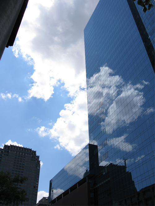 clouds in the sky and reflected on a steel and glass building