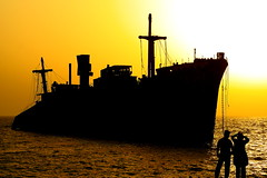 Persian Couple and Greek Ship in Persian Gulf (eshare) Tags: sea sky sun beach landscape persian couple ship iran silhouettes persia kish iranian  iranians persiangulf persians   kishisland   greekship    kakadoo takenfrombehind  sonyalphadslra100 sal50f14 sal5014  photofaceoffwinner naturessilhouettes pfogold  100 5014 sonysal50mmf14lens sonyalpha50mmf14lens