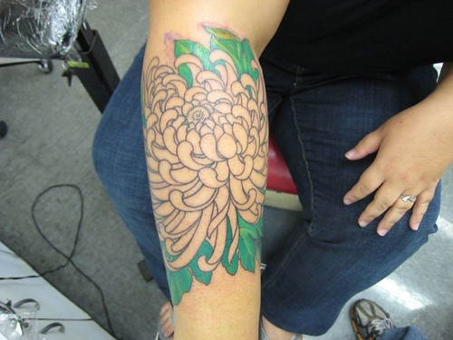outline of chrysanthemum tattoo and green leaves filled in so far