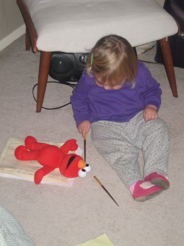 """Using her """"tools"""" to fix Elmo's eyes"""
