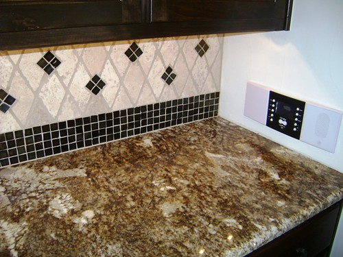 Granite and backsplash by Grand Installations LLC.