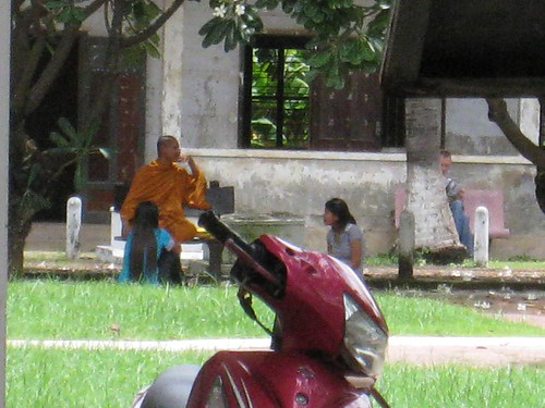 Children sit with a monk in the courtyard