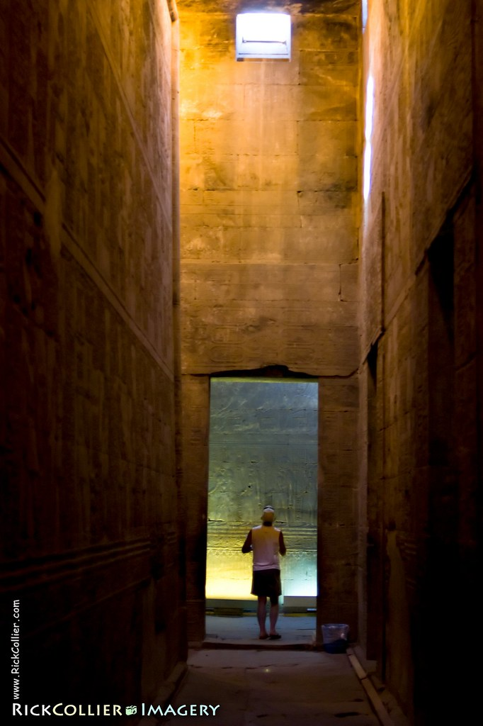 A tourist pauses in a doorway between chambers, dwarfed by the passage between temple walls within the Edfu Temple in southern Egypt