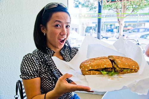 a woman holding a large sandwich