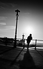 Under the lantern (Philipp Klinger Photography) Tags: light sea sky bw woman white black holland water netherlands clouds reflections pier bravo shadows counter scheveningen den hague bungee lantern haag northern philipp leaning lean the ballustrade klinger aplusphoto dcdead