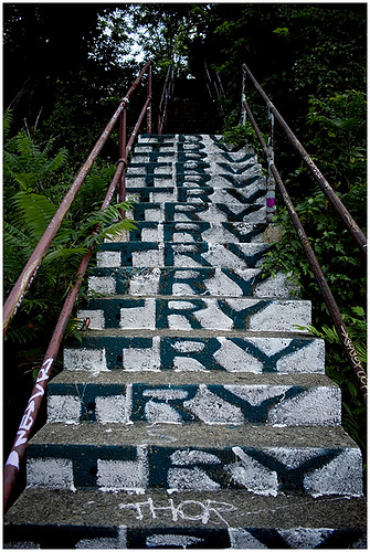 graffiti on a concrete, outdoor staircase: at the front of each step is painted the word Try, so it rises up as you climb: Try, Try, Try, Try, Try...
