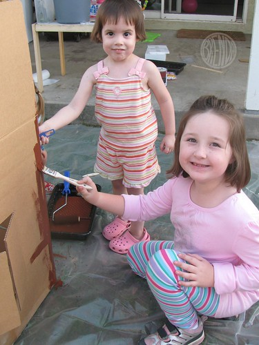 happy children painting large cardboard gingerbread house