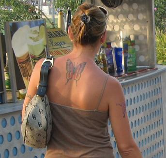 Like Mother, with designer purse and back and arm tats