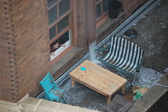 Apartment resident looks out as rain soaks her makeshift patio