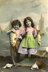 From a French tinted postcard (lovedaylemon) Tags: boy sea shells fish girl smile vintage french boats found seaside fishing child postcard images edwardian