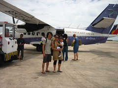 a large-foreheaded family in front of a small plane