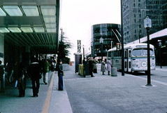 gm_10031 Granville Mall Bus Stop, Vancouver BC 1976 (CanadaGood) Tags: bc britishcolumbia vancouver downtown analog hbc eatons 1976 slidefilm granvillestreet kodachrome slidecube colour color bchydro bus streetphoto building person people sign canadagood canada seventies shopping text tree pavement