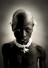 Karo boy with flowers Ethiopia (Eric Lafforgue) Tags: boy portrait black flower fleur face kara eyes artistic dam tribal hasselblad explore ornament bodypainting ethiopia tribe rite karo barrage tribo regards headdress adornment pigments headwear headgear tribu omo eastafrica thiopien etiopia ethiopie etiopa blackskin h3d lafforgue  etiopija ethiopi omoriver  artlibre etiopien etipia  etiyopya  kolcho artlibres nomadicpeople    korcho   06199 salinicostruttori    gibeiiidam gibe3dam bienvenuedansmatribu peoplesoftheomovalley