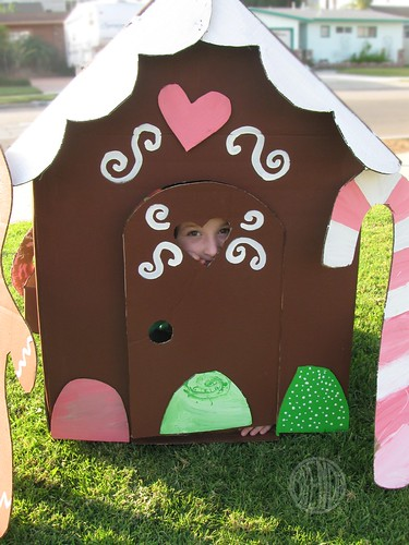 child peeking out of life size cardboard gingerbread house