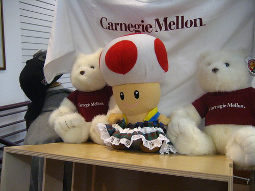 Toad is wearing a tartan garter sharing time with other plushes