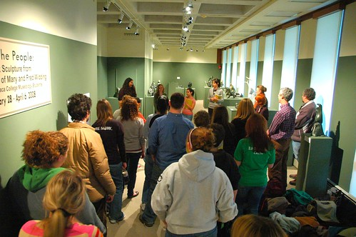 Visitors listen as JJ and other student curators describe the process of curating an art exhibition.