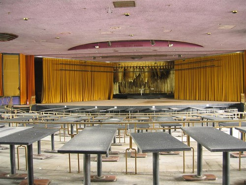 Empty tables by the stage of the Persian Room