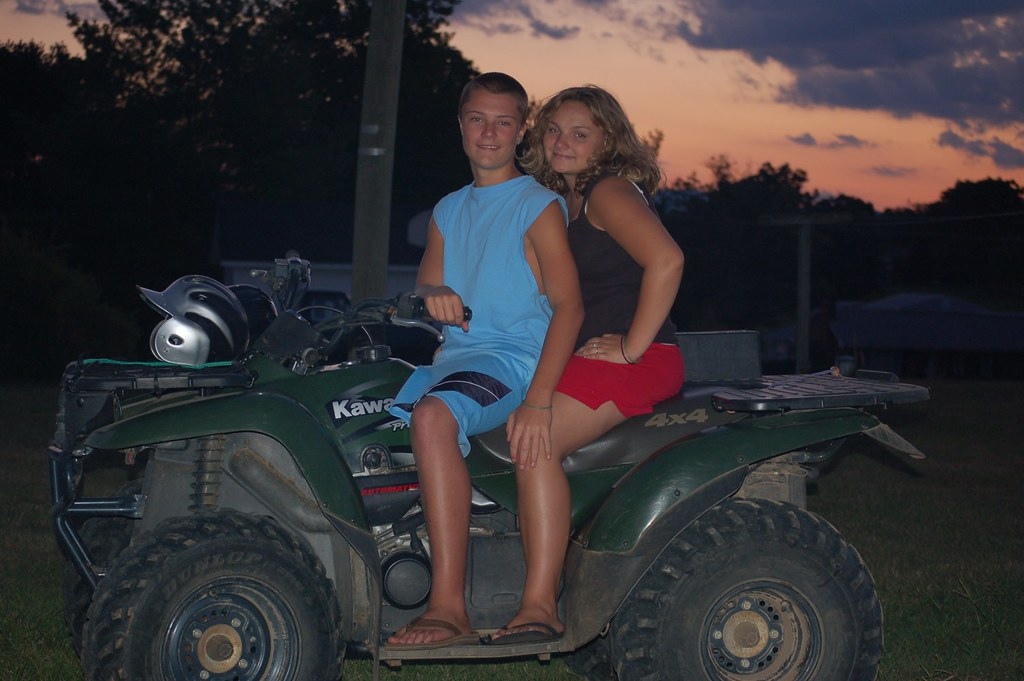 My daughter and her boyfriend on his 4-wheeler that she wrecked the other day and flattened the tire.