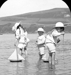 Girls and boys with model sailboats (oldsailro) Tags: park old boy sea summer people sun lake playing beach water pool girl sunshine youth sailboat race vintage children fun toy boat miniature wooden pond model waves sailing ship child time yacht antique group victorian boom mat regatta hull spectators watercraft adolescence keel fashioned