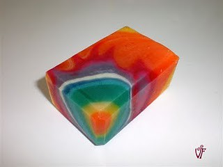 soap bar in rainbow colours. They are poured/swirled to look like a cutaway of concentric spheres of colour.