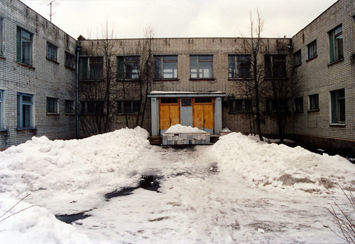 View of a Russian orphanage with snow, trees, and a main entrance.