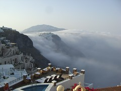 cloud rolling over Thira on the volcanic edge of Santorini in Greece