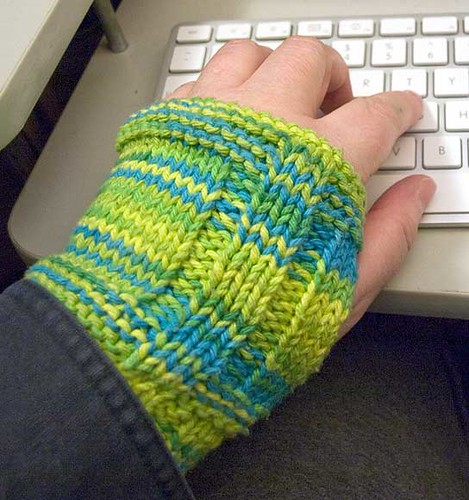 The fingerless mitt, which is bright blue, green, and yellow, on my hand.