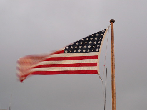 At the stern end of the flight deck, a remembered flag flaps in the breeze