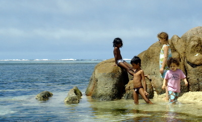 Local kids playing on granite rocks in Anse aux Courbes on Mahe (Seychelles)