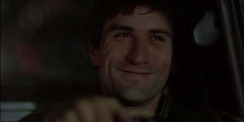 Fotograma de Robert de Niro en Taxi Driver sonriendo a través del cristal delantero de su Taxi