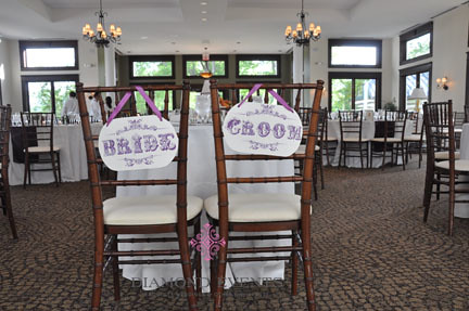 Bride & Groom signs on the back of the sweetheart table chairs