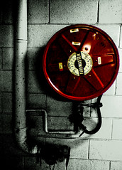 Fire Hose Reel ([ Kane ]) Tags: red blackandwhite black brick art texture photoshop real fire pipes grain australia brisbane hose qld kane firehose lightroom gledhill firehosereel firemaster kanegledhill firereelhose humanhabits wwwhumanhabitscomau kanegledhillphotography
