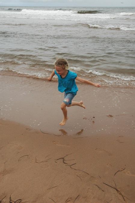 Sarah, airborne on Cavendish Beach