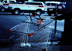 Dirty Trolley Pusher (PudgyCoconut) Tags: blue cars night shopping dark nikon dof arm d70 bokeh pavement trolley australia melbourne 4wd victoria sidewalk frame babyseat carpark footpath iso1600 theage wideopen 50mmf14d boomgate styrofoamcups ltlonsdalest mugley