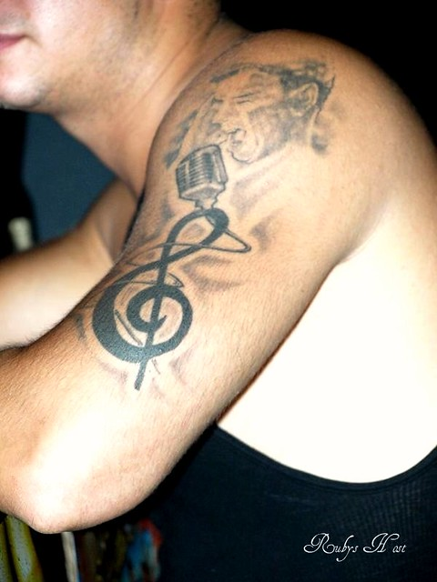 Musical notes and singer arm tattoo by Brooklyn Ink