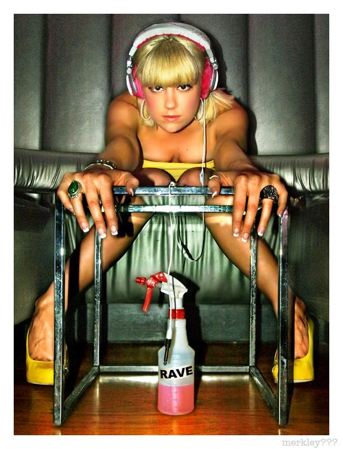 DJ Lea Luna - Seated in a Sticky Silver Nightclub Booth Sporting Yellow Gear With White and Fuzzy Pink Unplugged Headphones While Stretched Forward Over a Chrome & Glass Cocktail Table & a 2/3 Empty Squirt Bottle of Matching Pink Rave Juice