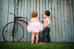 Cute little couple (By Faith Photography) Tags: grass bluejeans tutu redchucks ilovemyjob noshirts bluefence oldfashionedtricycle barebellies littlegirllittleboy mymompaintedthefenceprettyhuh peekaboochildrensboutique