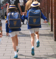 Skipping Schoolgirls outside Victoria Station, London (UGArdener) Tags: blue england streets london english unitedkingdom britain pigtails schoolgirls sidewalks streetscenes pimlico chlidren victoriastation schooluniforms bookbags happychildren skippingschoolgirls skyblueshoes englishtravel