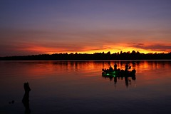 The Water's on Fire (Canicuss) Tags: blue trees sunset orange lake black reflection green water silhouette yellow night clouds landscape boat fishing ripple horizon ripples fabulous fishingboat shimmer blueribbonwinner colorphotoaward colourartaward artlegacy thewatersonfire canicuss