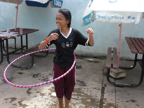 A person grinning and using a hula hoop.
