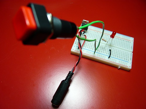 Breadboard with power jack, voltage regulator, push-button switch, and LED
