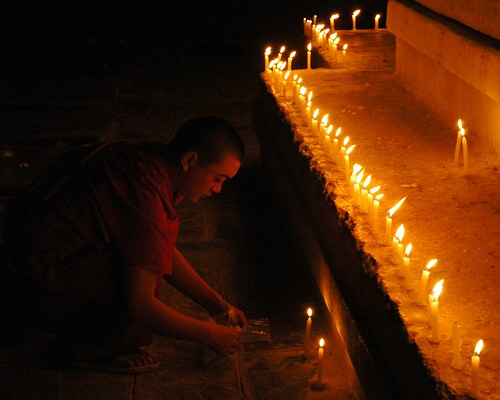 Monk lighting candles on a stupa east side of Boudha, Kathmandu, Nepal
