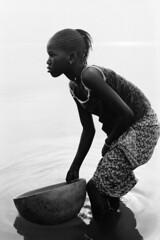 Girl with Calabash (longboy74) Tags: leica portrait blackandwhite lake film vertical bowl skirt westafrica braids mali washing calabash bendingdown wadinginwater lacdebo youngblackgirl