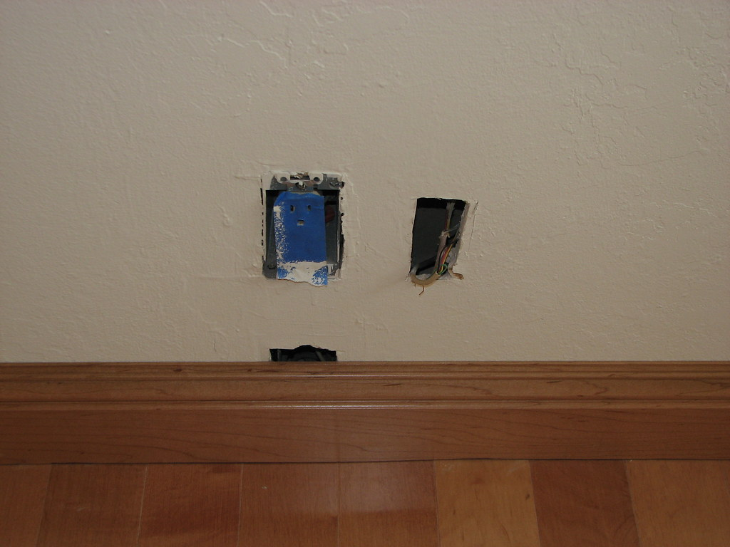 Baseboard partially covers old phone jack box - 009